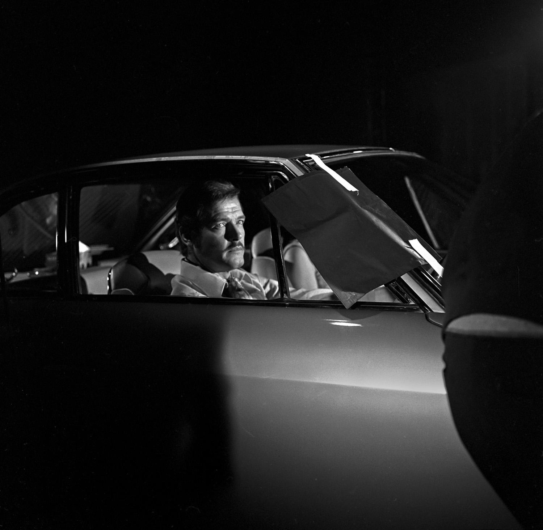 """© Rolf Adlercreutz Titel: Roger Moore/""""Helgonet""""  Plats/datum: Elstree Studios London 1969Bildmått: 40x40 cm Teknik: Arkivbeständig pigmentbläckutskrift Montering: Träram med passepartout 50x50 cm Upplaga: 15 Signerad: Ja  Pris: 4900 SEK"""