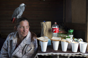 KRUGERSDORP, SOUTH AFRICA - JULY 18: An Afrikaner women poses for a photo with her parrot in Munsieville township on July 18, 2018 in Krugersdorp a suburb in Johannesburg, South Africa. This black township, where South Africans and African immigrants live, now also has a separate section of poor white Afrikaners. They live side my side but they don't mix unless they have too. Many of the residents survive by begging at traffic lights and doing odd jobs. Today it was Mandela day and they received donations of food. (Photo by Per-Anders Pettersson/Getty Images)