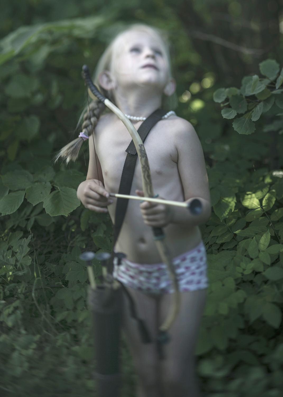 """© Anna Claren Titel: The girl with the arrow,  Från serien """"När allt förändrades"""", 2018 Bildmått : 15x21 cm Teknik: Arkivbeständig pigmentbläckutskrift  Montering: Träram med passepartout 30x40 cm Upplaga: 5 + 2 AP   Signerad: Ja   Pris: SEK 20 000"""